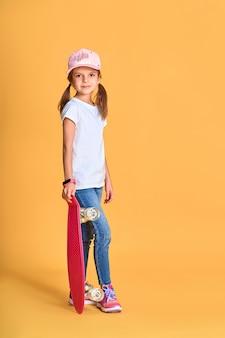 Stijlvolle grappig meisje draagt een wit t-shirt, blauwe spijkerbroek en sneakers, met skateboard over gele muur