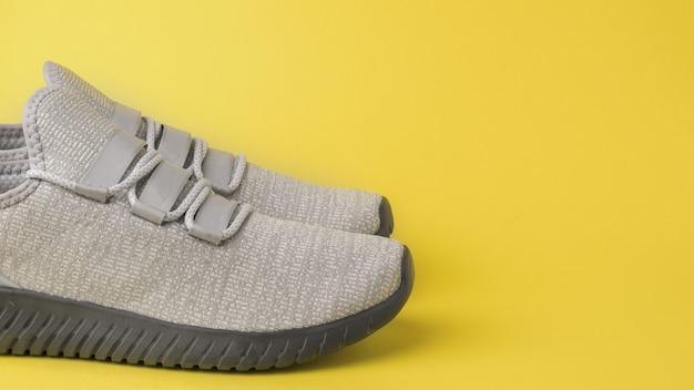 Stijlvolle grijze unisex sneakers op een gele achtergrond. sportieve levensstijl. kleuren 2021.