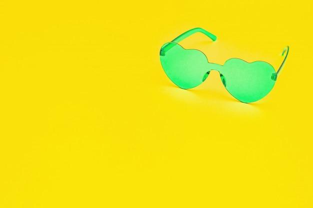 Stijlvolle hartvormige bril op gele achtergrond met kopie ruimte. mooie trendy turquoise zonnebril. mode zomer concept.