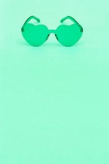 Stijlvolle hartvormige bril op groene achtergrond met kopie ruimte. mooie trendy zachtgroene zonnebril. mode zomer concept. afbeelding in verticaal formaat.