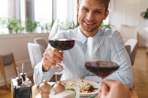 Stijlvolle heer die een glas alcoholische drank vasthoudt en naar de dame met een glimlach kijkt terwijl hij aan tafel zit met heerlijk eten