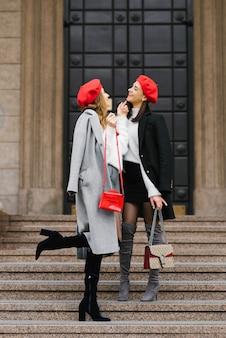 Stijlvolle, heldere meisjesvriendinnen in rode baretten en herfstjassen lopen door de stad en lachen