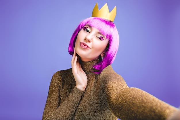 Stijlvolle heldere selfie portret modieuze jonge vrouw vieren feest. knip paars haar, aantrekkelijke make-up met tinsels, kus geven, vrolijke emoties, verjaardag, vakantie.