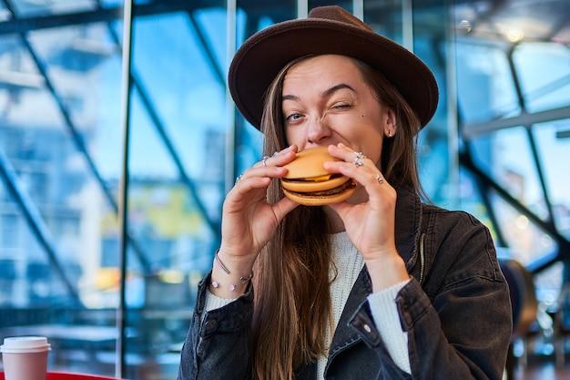 Stijlvolle hipster hongerige vrouw eet hamburgerbroodje met rundvlees in fastfoodrestaurant