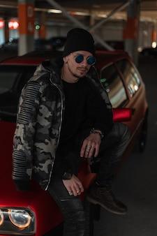 Stijlvolle hipster man met mode zonnebril in stedelijke militaire jas, pullover, jeans en hoed staat in de buurt van rode auto in de stad