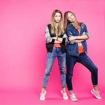 Stijlvolle hipster twee die zich met gekruiste handen bevinden en bij roze stellen.