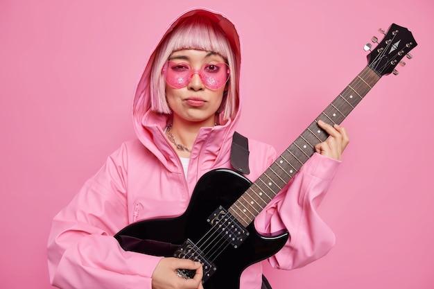 Stijlvolle hipster vrouw draagt trendy zonnebril jas met capuchon poses met zwarte elektrische gitaar ziet er serieus uit, maakt nieuw nummer voor haar album