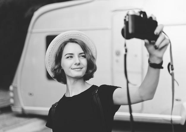 Stijlvolle hipster vrouw in hoed maakt selfie portret met retro camera. zwart-wit foto