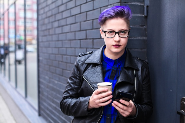 Stijlvolle hipster vrouw met behulp van een telefoon sms'en op smartphone app in een straat met papieren kopje koffie
