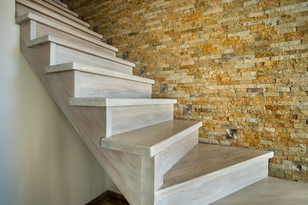 Stijlvolle houten eigentijdse trap binnen loft huis interieur. moderne hal met decoratieve kalkstenen muren en wit eiken trappen.