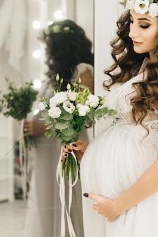Stijlvolle jong zwanger meisje in witte kleren met krullen en bloemen. foto's wachten op baby