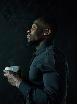 Stijlvolle jonge afrikaanse zwarte man met witte kop koffie poseren op donkere studio achtergrond.