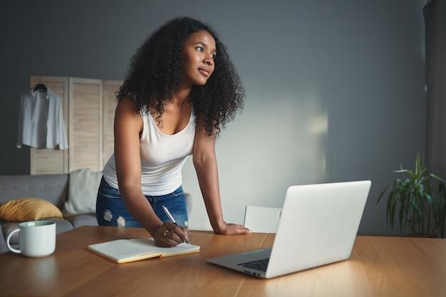 Stijlvolle jonge afro-amerikaanse vrouw journalist met krullend haar permanent aan bureau met geopende laptop en opschrijven in voorbeeldenboek, onderzoek doen voor nieuw artikel. mensen, beroep en technologie