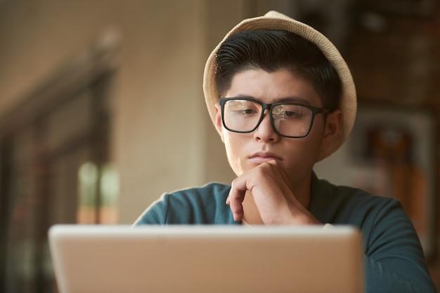 Stijlvolle jonge aziatische man in hoed en bril in café zitten en kijken naar het scherm
