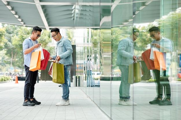 Stijlvolle jonge aziatische man toont zijn aankoop aan opgewonden vriend wanneer ze op straat staan