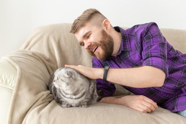 Stijlvolle jonge bebaarde man hipster streelde zijn mooie grijze scottish fold kat zittend op de bank