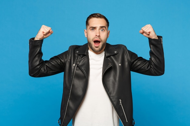 Stijlvolle jonge, bebaarde man in zwart lederen jas wit t-shirt met biceps, spieren geïsoleerd op blauwe muur achtergrond studio portret. mensen oprechte emoties levensstijl concept. bespotten kopie ruimte.