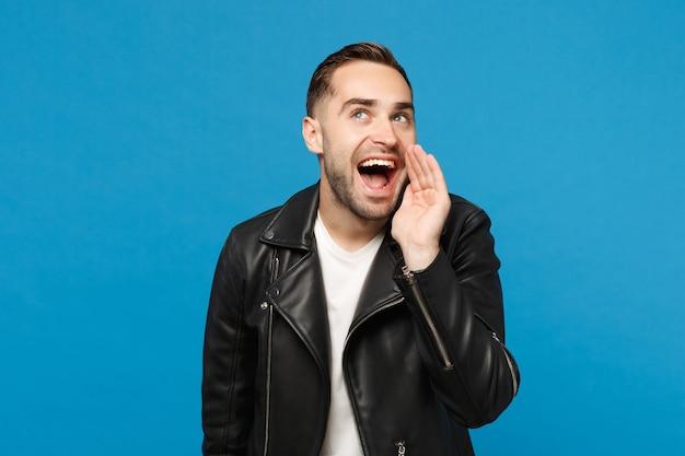 Stijlvolle jonge, bebaarde man in zwart lederen jas wit t-shirt schreeuwen, hand naar mond geïsoleerd op blauwe muur achtergrond studio portret. mensen oprechte emoties levensstijl concept. bespotten kopie ruimte