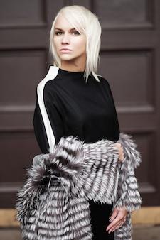 Stijlvolle jonge blonde vrouw met een winterse look
