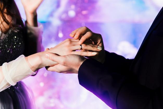 Stijlvolle jonge bruid en bruidegom uitwisselingsringen. het concept van bruiloft decor in ruimte stijl