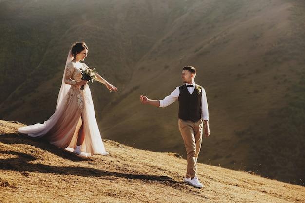 Stijlvolle jonge bruidspaar heeft plezier poseren in prachtige georgische bergen