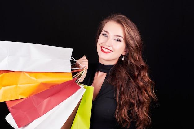 Stijlvolle jonge brunette vrouw met kleurrijke boodschappentassen