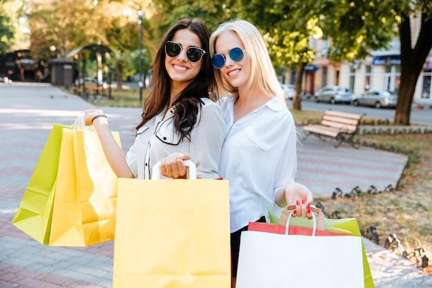 Stijlvolle jonge dames in zonnebrillen lopen over straat met boodschappentassen