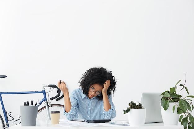 Stijlvolle jonge donkere vrouwelijke accountant in brillen en shirt werken vanuit huis