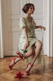 Stijlvolle jonge elegante dame in gebloemde jurk en rode hoge hakken zit op transparante stoel in de buurt van witte deuren en heeft prachtige heldere bloemen
