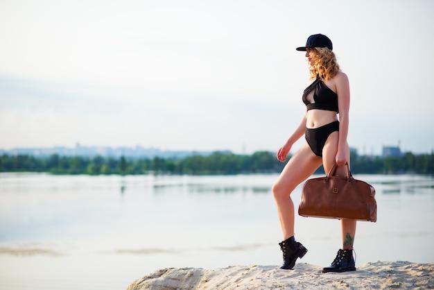 Stijlvolle jonge en mooie vrouw in een zwart ondergoed draagt een pet en leren laarzen met een leren tas zit op een zandgroeve op een zonnige warme zomerdag