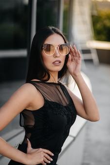 Stijlvolle jonge en sexy meisje poseren voor een business center in zwart. mode en stijl