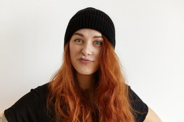 Stijlvolle jonge europese vrouw met slordig kapsel, gekleed in zwarte hoed en t-shirt pruilende lippen