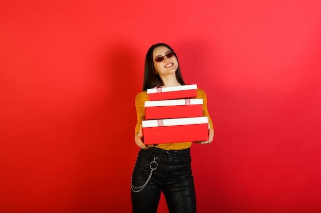 Stijlvolle jonge gelukkig lachende vrouw in rode zonnebril houdt drie rood-witte geschenkverpakkingen geïsoleerd op rood studiooppervlak.