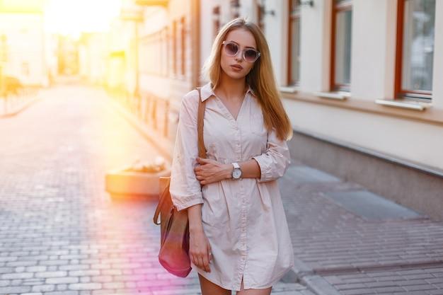 Stijlvolle jonge hipster vrouw in trendy zonnebril in een modieuze zomerjurk in witte sneakers met een stijlvolle lederen handtas staat in de stad op een warme zonnige dag bij zonsondergang. Premium Foto