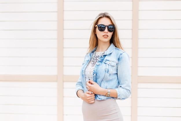 Stijlvolle jonge hipster vrouw in zwarte zonnebril in trendy denim blauw jasje poseren in de buurt van een houten vintage wit gebouw buiten op een zomerdag