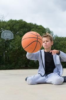 Stijlvolle jonge jongenstiener speelt buiten met bal ball