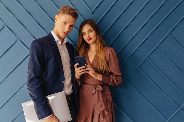 Stijlvolle jonge kerel met laptop en meisje met telefoonemoties, aquaachtergrond