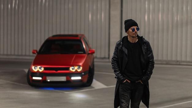 Stijlvolle jonge knappe man in modieuze zwarte kleding met een leren jas en een hoodie met zonnebril loopt in de buurt van een rode auto op een parkeerplaats