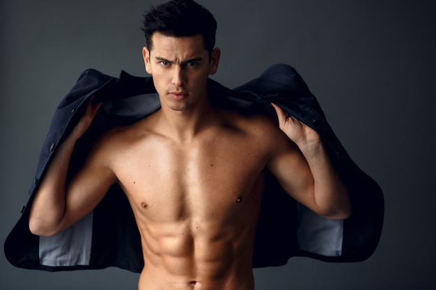 Stijlvolle jonge knappe man permanent en poseren in modieus pak op een naakte torso