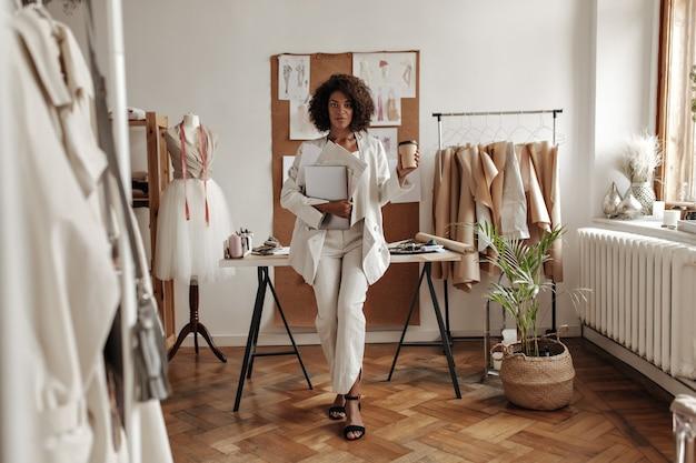 Stijlvolle jonge krullende donkere vrouw in witte broek, jas en blouse leunt op bureau in modeontwerper kantoor, houdt koffiekopje en laptop