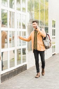 Stijlvolle jonge man die buiten het gebouw praten op mobiele telefoon