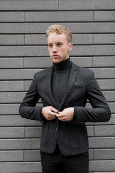 Stijlvolle jonge man die het jasje schikt