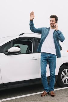 Stijlvolle jonge man die in de buurt van de moderne auto zwaait met zijn hand