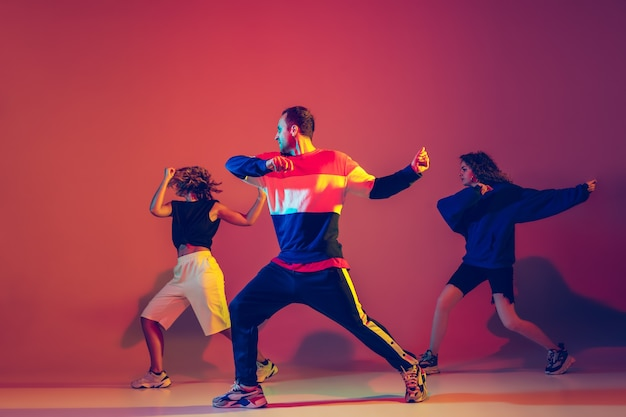 Stijlvolle jonge man en vrouw die hiphop dansen in lichte kleding op een achtergrond met kleurovergang in de danszaal in neonlicht. jeugdcultuur, beweging, stijl en mode, actie, hiphop. modieus portret.