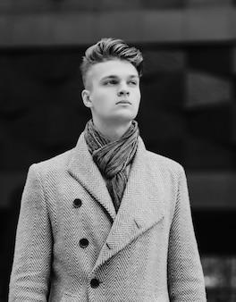 Stijlvolle jonge man in een jas. zwart-wit opname