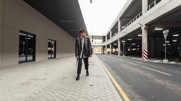 Stijlvolle jonge man in een oversized leren jas in vintage broek in coole laarzen met een modieuze zwarte rugzak loopt op straat in de buurt van de parkeerplaats. aantrekkelijke man in trendy kleding buitenshuis.