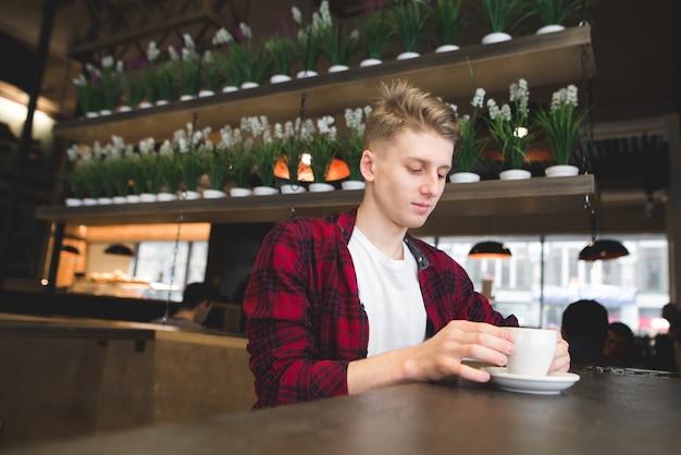 Stijlvolle jonge man in een rode prullenbak zit in een café met een kopje koffie.