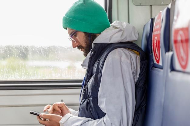 Stijlvolle jonge man in glazen zit in een treinwagon met markeringen voor passagiers zitten en kijkt naar een smartphone.