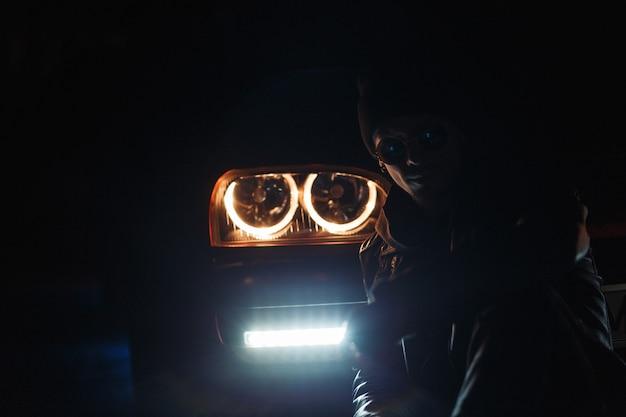 Stijlvolle jonge man in modieuze zonnebril met een leren jas en een hoed zit in het donker in de buurt van een auto met felle koplampen