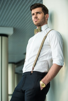 Stijlvolle jonge man is poseren in modern gebouw.